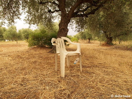 Broken old plastic chair under oliv trees in Greece